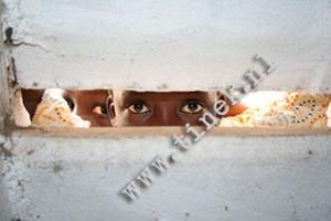 Ghanees meisje kijkt dor raam verkleind